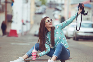 woman in blue clothes on skateboard taking selfie