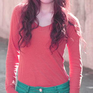 woman in red long sleeve shirt with green pants