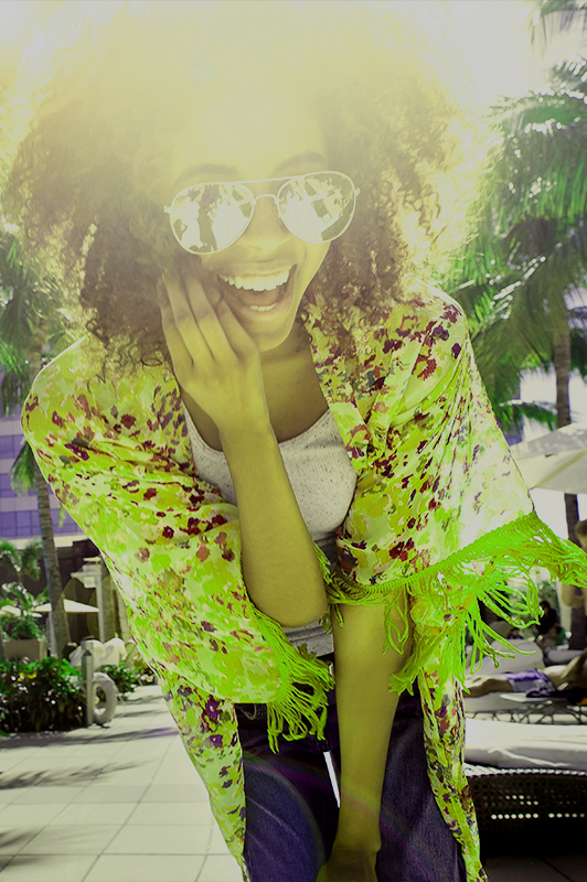 Girl with sunglasses laughing.