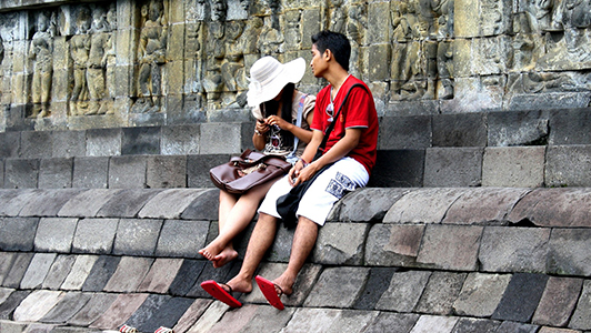 Girl with a hat sitting on a wall with a guy in red tee shirt.