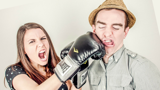 A girl punching a guy in the face.