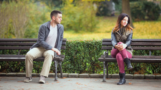 two people sitting in separate benches