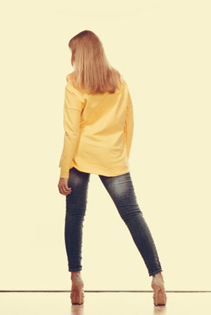 woman in long sleeve yellow shirt and faded jeans facing away