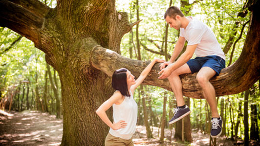woman looking up at man siting in tree