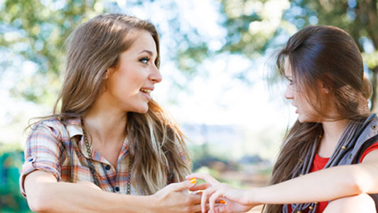 two friends talking outdoors