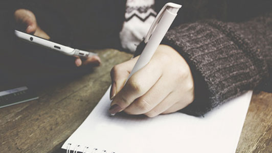 woman holding phone writing in notebook with white pen