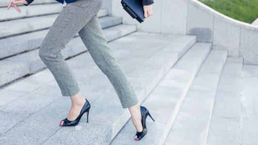 business woman in black high heels walking up steps
