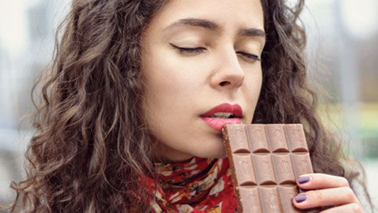 woman savoringly eating chocolate bar