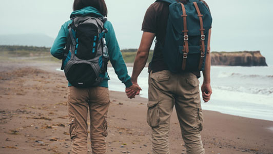 traveler couple holding hands at beach