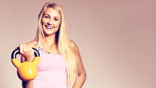 smiling woman holding kettlebell