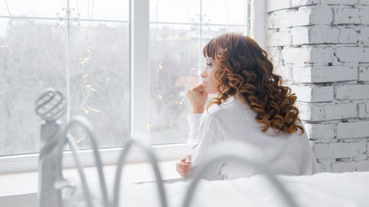 woman thinking in white room looking out window