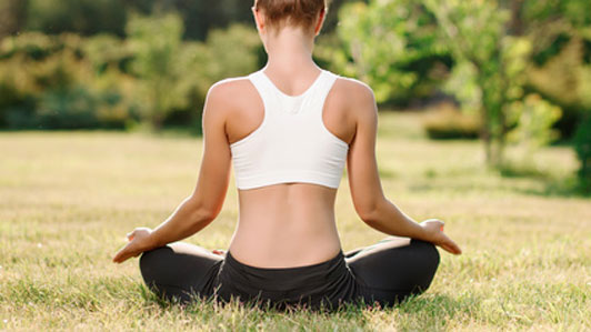 back of woman practicing yoga in grass