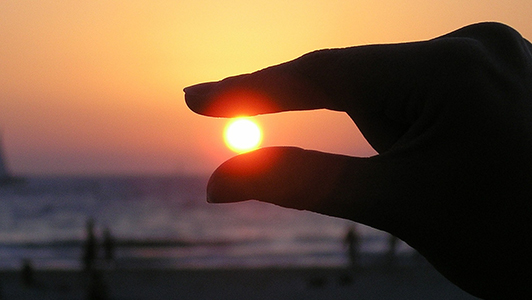 Girl holding her fingers so that it looks like she's holding Sun setting.