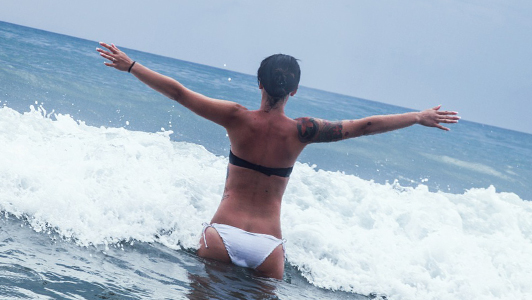 Girl in a black and white bikini holding her arms spread while standing in water.