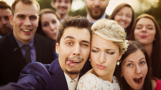 couple in wedding trying to take selfie
