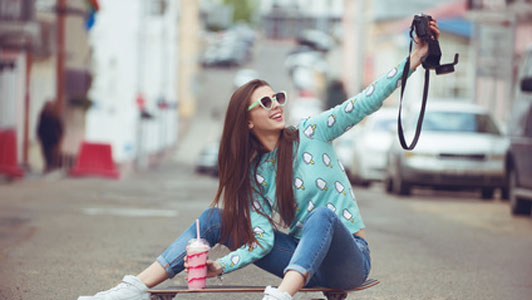 young woman wearing sunglasses sitting on skateboard drinking shake taking picture of self