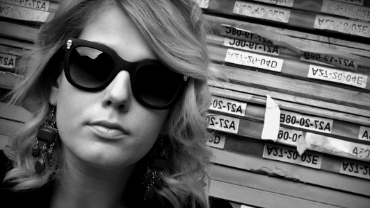 Black and gray photo of a blonde girl with sunglasses and big earrings.