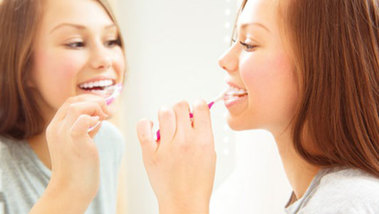woman and reflection brushing teeth