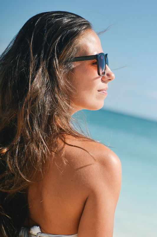 A girl with sunglasses standing on a beach.