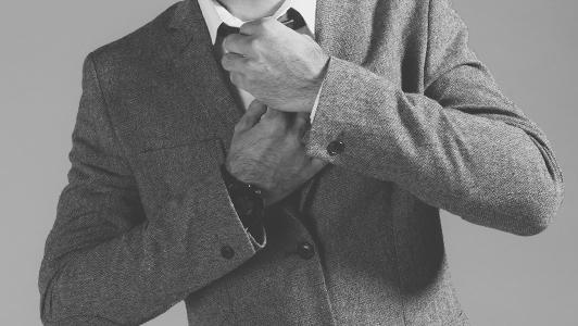 A man in a suit adjusting his tie.