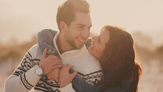woman hugging man in sweater outdoors