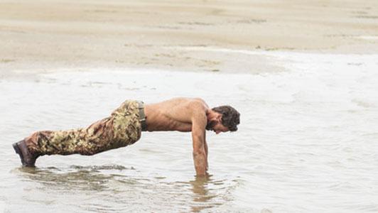 man in camo doing push ups on shore