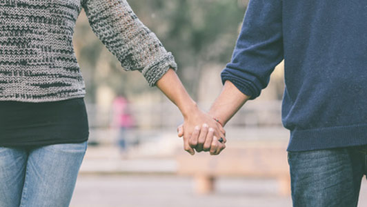couple wearing jeans holding hands in middle of park