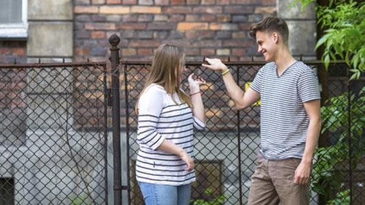 girl facing guy outside talking