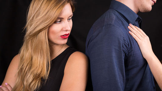 woman looking behind back at arm on unfaithful man
