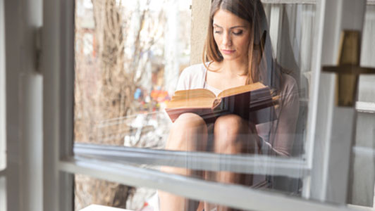 woman reading on windowsill
