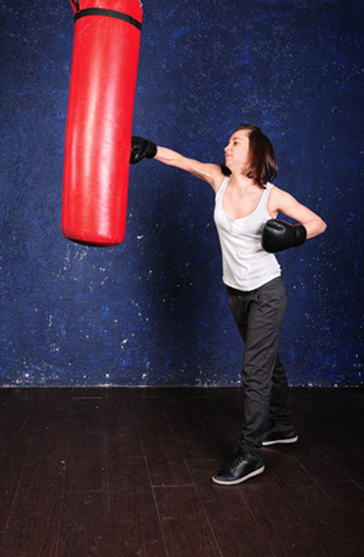 woman venting out at punching bag