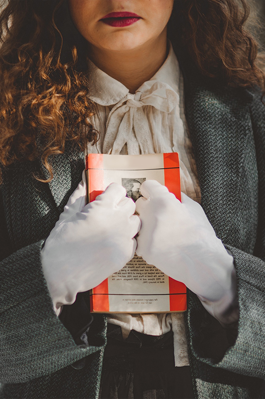A woman with white gloves holding a book against her chest.