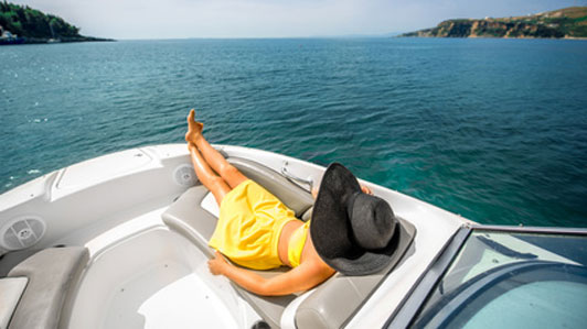 woman in large black hat relaxing on yacht
