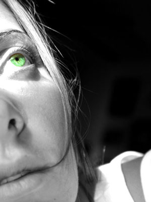woman with green eyes looking up at something