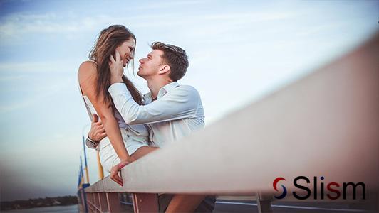 romantic couple sitting on a bridge