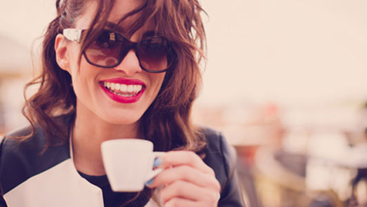 woman holding small cup smiling big