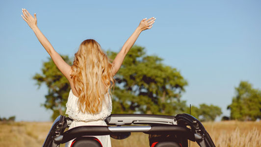 woman standing up with arms held up in convertible