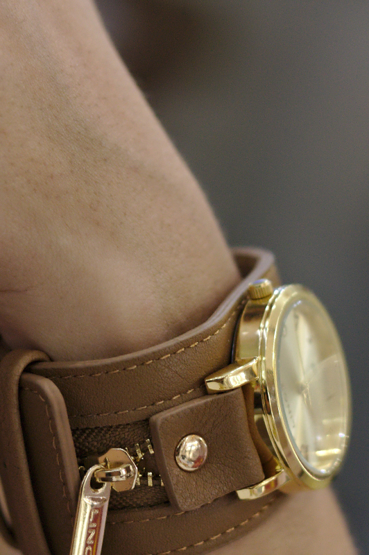 Close-up of a leather and gold watch.