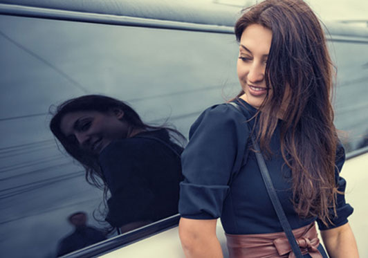 young woman leaning on car looking at reflection of guy approaching