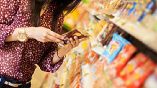 young woman looking at food label