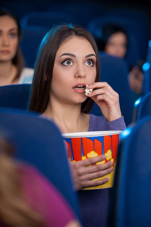 girl eating popcorn at movies