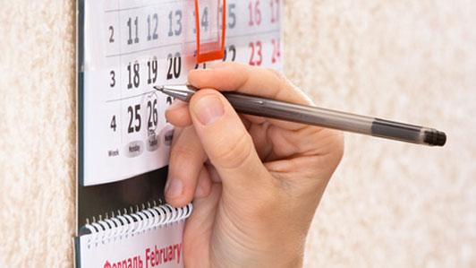 woman marking date on calendar