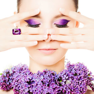 purple eye shadow woman wearing ring cropping eyes with fingers