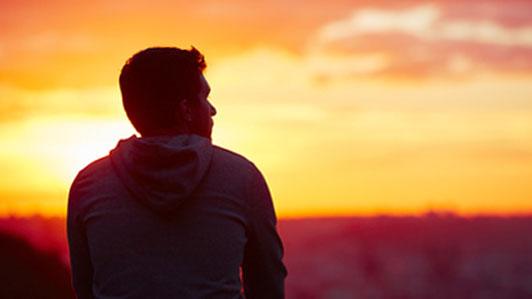 sunrise man sitting alone thinking