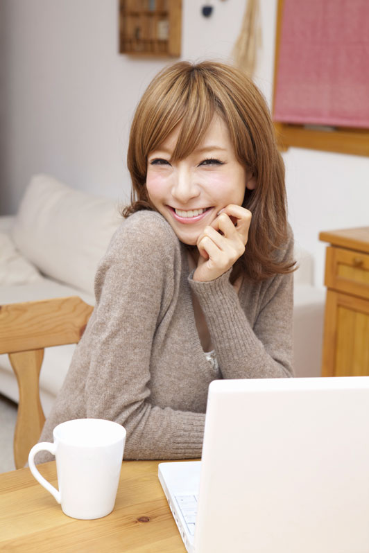 girl in front of laptop smiling with warm beverage