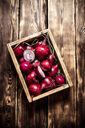 box of red onions on wooden table