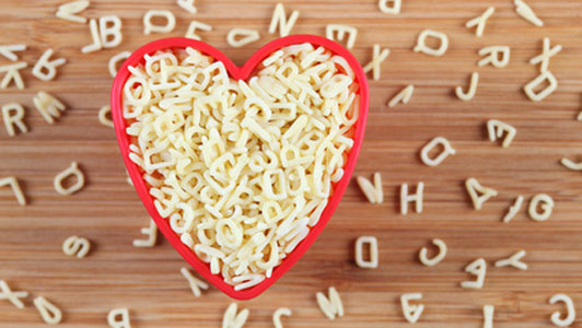 alphabet pasta in heart shaped red bowl