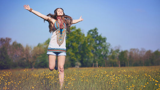 free woman in field jumping