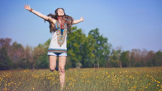free woman in field jumping