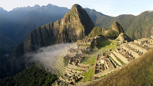 A view of terraced Machu Picchu and a cloud